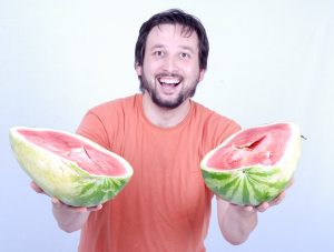 Caucasian man offers a watermelon